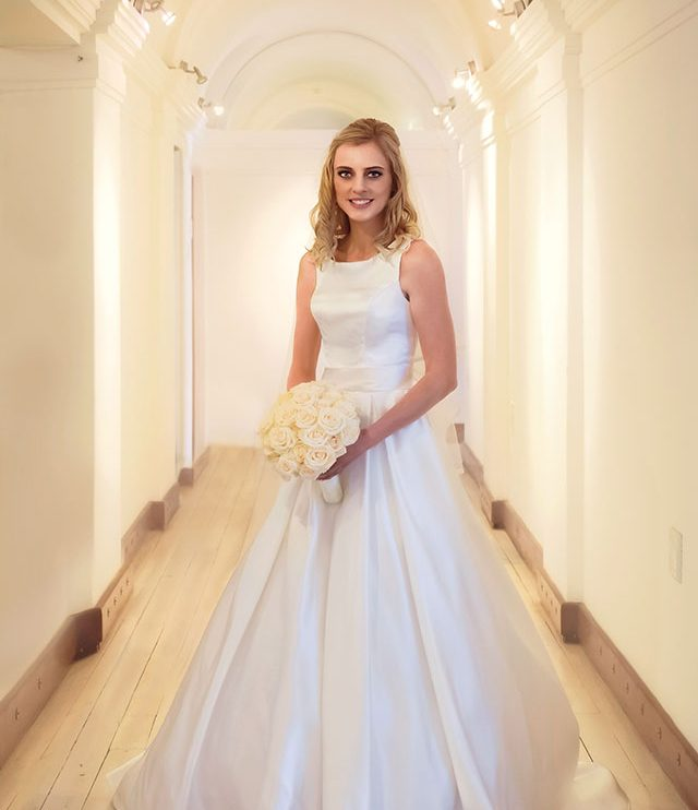 Wedding Photograph of bride standing in hallway
