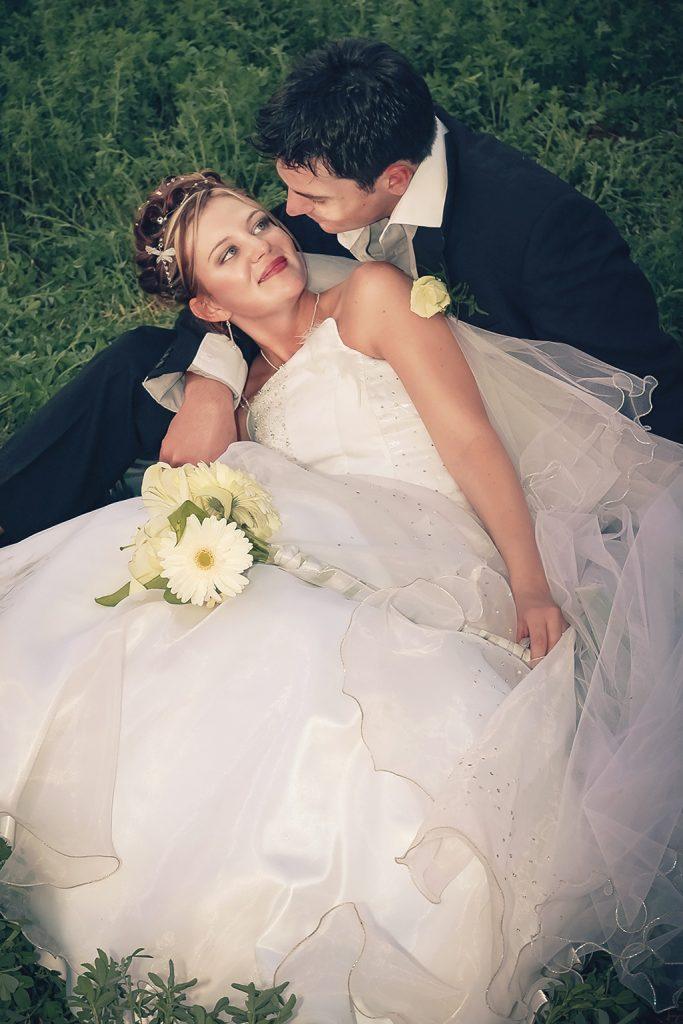 romanitc wedding photograph of couple sitting on grass