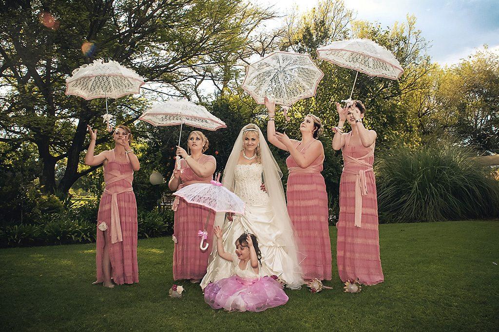 wedding photograph bridal party holding umbrellas